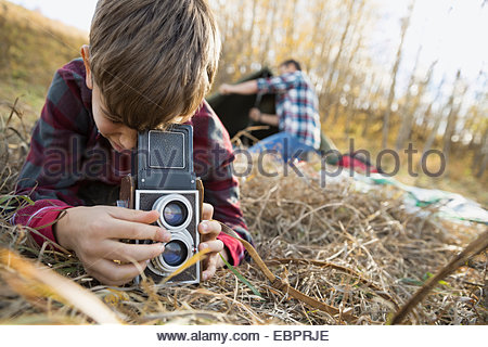 Boy using retro camera at campsite - Stock Photo