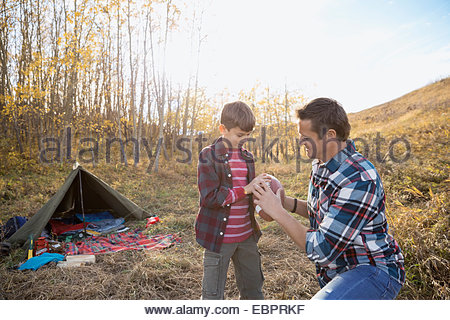 Father and son with football at campsite - Stock Photo