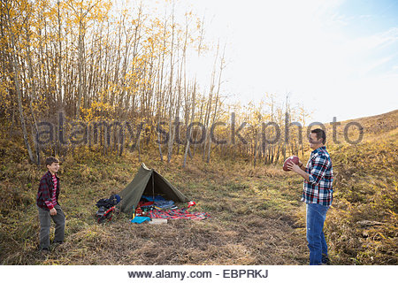 Father and son playing football outside campsite - Stock Photo