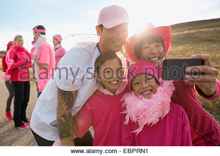 Family in pink taking selfie at charity race - Stock Photo