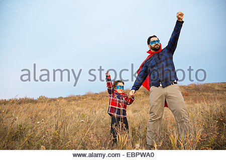 Father and son in superhero capes in field - Stock Photo