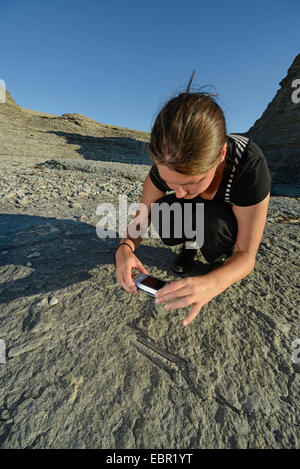 young woman taking photos of fossils at Byrum's raukar, Sweden, Oeland, Byrums Raukar - Stock Photo