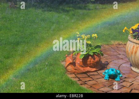 garden with flowers and rainbow, Germany - Stock Photo