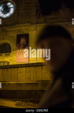 ActiveMuseum_0002782.jpg / A passer-by in front of the Musee d'Orsay at night. The poster of the exhibition Ange - Stock Photo