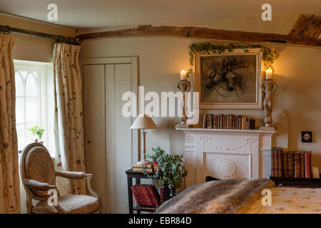 Louis XVI chair in cottage bedroom with fireplace and antique books - Stock Photo