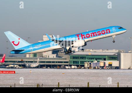 Thomson Airways Boeing 757-200 climbs away from a snow covered runway 05L at Manchester airport. - Stock Photo