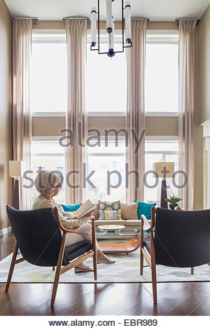 Woman reading book in modern living room - Stock Photo