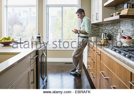 Man text messaging on cell phone in kitchen - Stock Photo