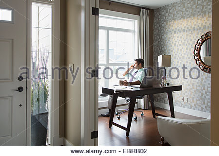 Man talking on cell phone in home office - Stock Photo