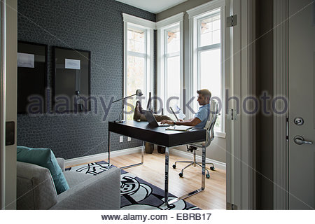 Man reading with feet up in home office - Stock Photo