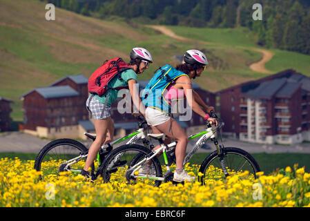 two mountain bikers biking through a flower meadow, hotels in background, France, Savoie, La Plagne - Stock Photo