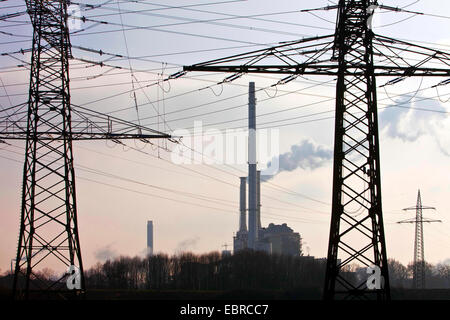 power poles with high voltage power lines and industry, Germany, North Rhine-Westphalia - Stock Photo