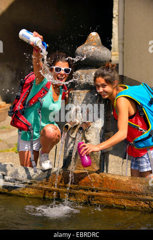 two young female hikers refreshing at a fountain, France, Savoie - Stock Photo