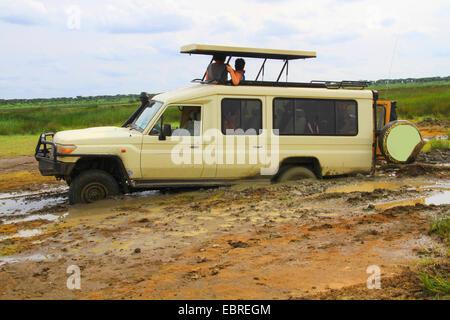 safari car sticking fast in the mud, tourists waiting for help, Tanzania, Serengeti National Park - Stock Photo