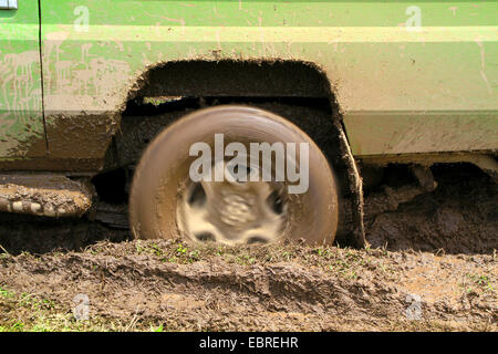 spinning wheel of a safari car sticking in the mud, Tanzania, Serengeti National Park - Stock Photo