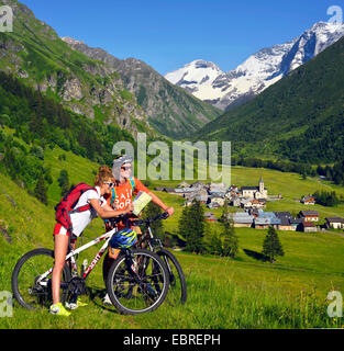 two mountain bikers looking at a map in front of scenic mountain scenery, France, Savoie, Vanoise National Park, - Stock Photo