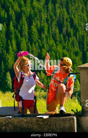 two wanderers refreshing at a fountain, France, Savoie, Vanoise National Park, Champagny - Stock Photo