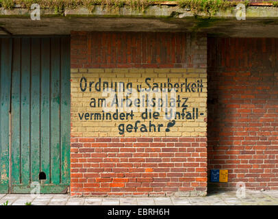 appeal for order and cleanness at the workplace at the facade of an old silo, Germany - Stock Photo