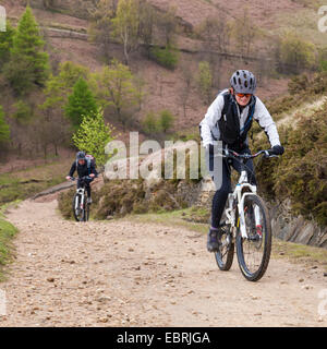 Mountain biking in the UK. Cyclists cycling on an up hill path on the north side of Jaggers Clough, Derbyshire, - Stock Photo