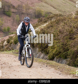 Woman cyclist cycling up the north side of Jaggers Clough, Derbyshire, Peak District, England, UK - Stock Photo