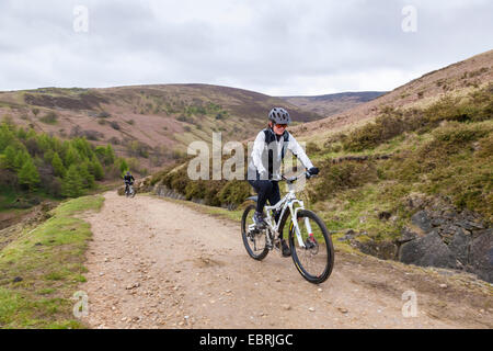 Woman cycling up a hill on a stony track. Jaggers Clough, Derbyshire, Peak District, England, UK - Stock Photo