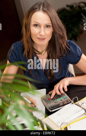 young woman sitting at her desk checking her bank statements - Stock Photo