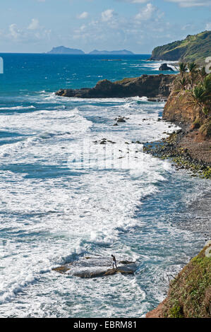 view along the rock coast with a fisherman standing on a rock in the surf, Saint Vincent and the Grenadines, Biabou - Stock Photo