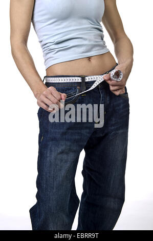 midsection of a young woman who has wrapped a measuring tape around her hips - Stock Photo