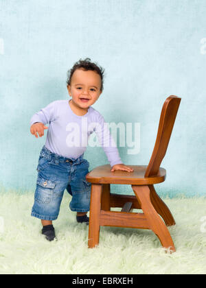 Adorable African baby boy trying to stand with help of a chair - Stock Photo