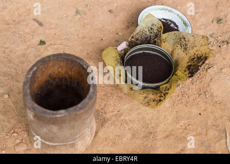 Indonesian roasted black coffee beans ground by hand in terracotta mortar. Selective focus. - Stock Photo