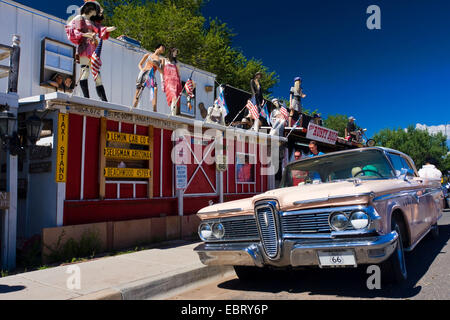 pink cadillac in front of souvenir shop decorated with display dummies, USA, Arizona, Seligman - Stock Photo