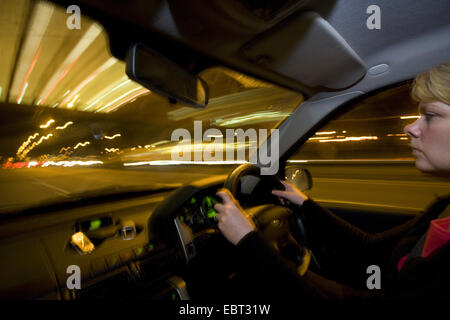woman driving at night on motorway, United Kingdom, England - Stock Photo