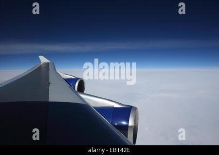 view through a wing of airplane Boeing 747 to the clouds and the sky - Stock Photo