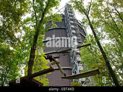 woman climbing on climbing crag in front of gasometer Oberhausen, Germany, North Rhine-Westphalia, Ruhr Area, Oberhausen - Stock Photo