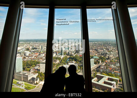 two people looking out of the window of Rheinturm to the city, Germany, North Rhine-Westphalia, Duesseldorf - Stock Photo
