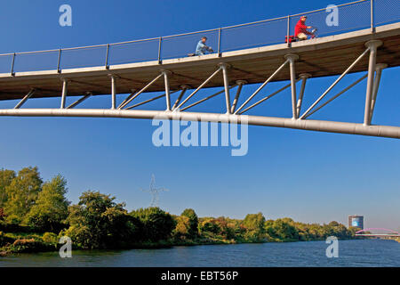 two cyclists on bridge over Rhine-Herne Canal attree and shrub garden Gehoelzgarten Ripshorst, Germany, North Rhine - Stock Photo