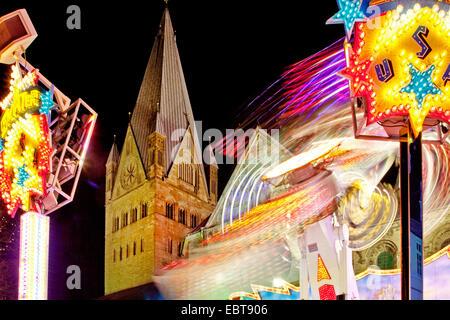 fun fair Allerheiligekirmes in front of St Patrokli cathedral in Soest at night, Germany, North Rhine-Westphalia, - Stock Photo
