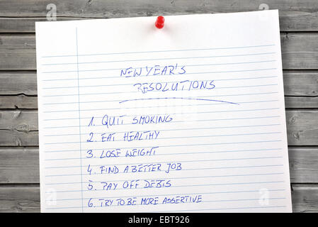 New Year's resolutions list on wooden background - Stock Photo