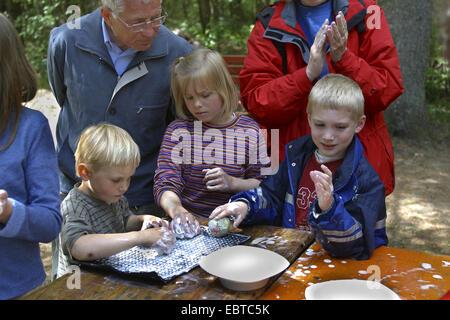 children felting sheep wool, Germany - Stock Photo