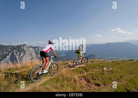 young couple mountain biking in the Alps at Lake Garda - Stock Photo
