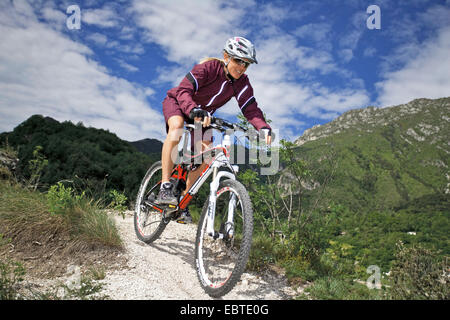 young biker on a mountain path in the Alps at Lake Garda - Stock Photo