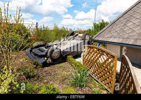 car lying on the roof in a garden after a traffic accident - Stock Photo
