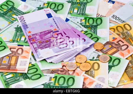 Many Euro banknotes and coins of the European Union - Stock Photo