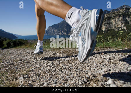 legs of a man jogging on a gravel road at Lake Garda, Italy - Stock Photo