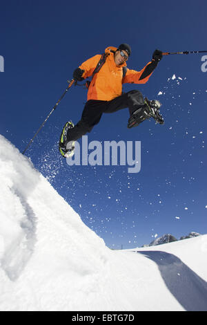 man wearing snow shoes in a snow-covered landscape jumping over a gap, Austria - Stock Photo