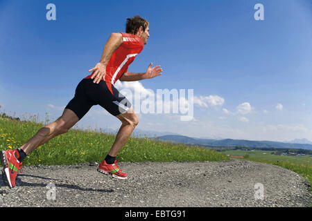 man running running on a gravel road in a mountain landscape, Italy - Stock Photo