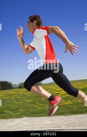 man running running on a gravel road, Italy - Stock Photo