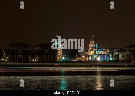 The Old Royal Naval College in Greenwich, London seen at night from across the River Thames as a boat passes by - Stock Photo