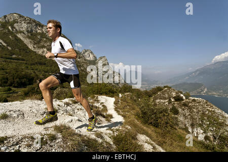 man jogging in the mountains high above Lake Garda, Italy - Stock Photo