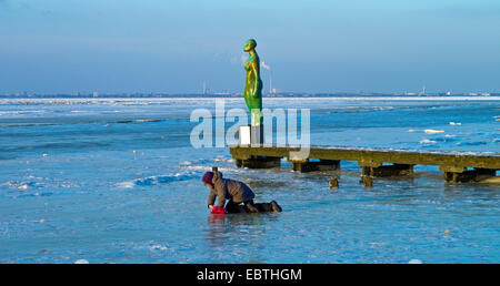 child playing on the ice in front of sculpture and the panorama of the icy Jade Bay in front of Wilhelmshaven, Germany, - Stock Photo